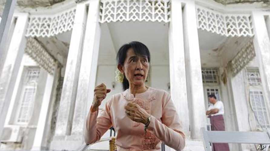 Pro-democracy leader Aung San Suu Kyi talks to reporters at her home in Yangon, July 11, 2011