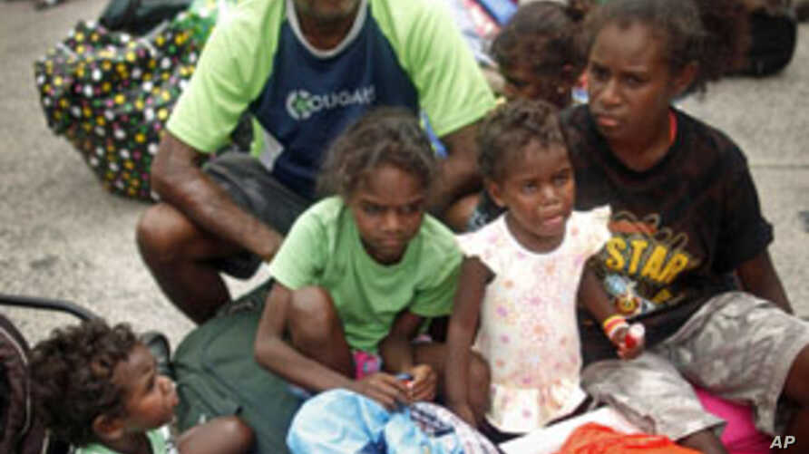 Local resident Selwyn Hughes (C) sits with his children outside an emergency cyclone shelter after it was declared full and the gate locked in Cairns, February 02, 2011