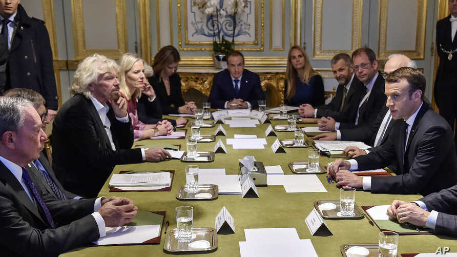 French President Emmanuel Macron, right, meets with US businessman Michael Bloomberg, left, Microsoft co-founder Bill Gates Bill Gates, British entrepreneur Sir Richard Branson, third left, and other philanthropists at the Elysee Palace in Paris, Dec