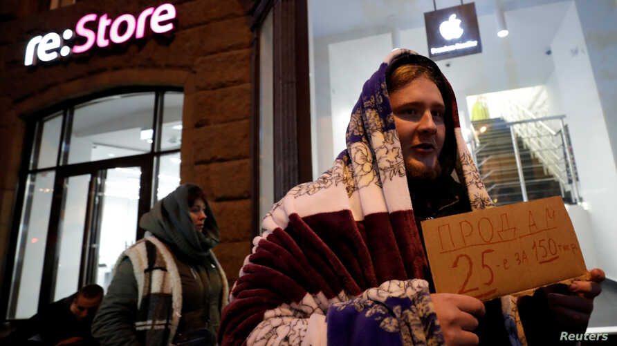 A man holds a sign about selling his place in line before the Apple's new iPhone XS and XS Max go on sale in front of a cell phone store in central Moscow, Russia Sept. 26, 2018.
