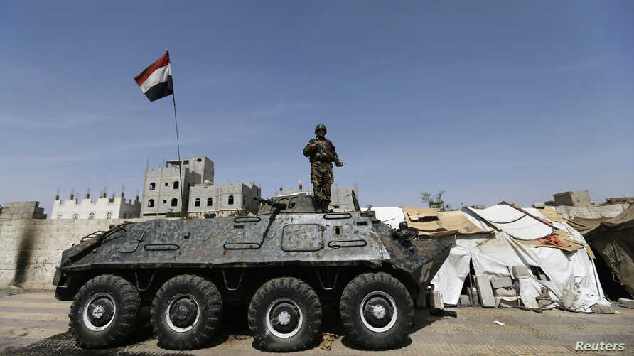 A police trooper stands on an armoured personnel carrier (APC) at a checkpoint in Sanaa, May 14, 2014.