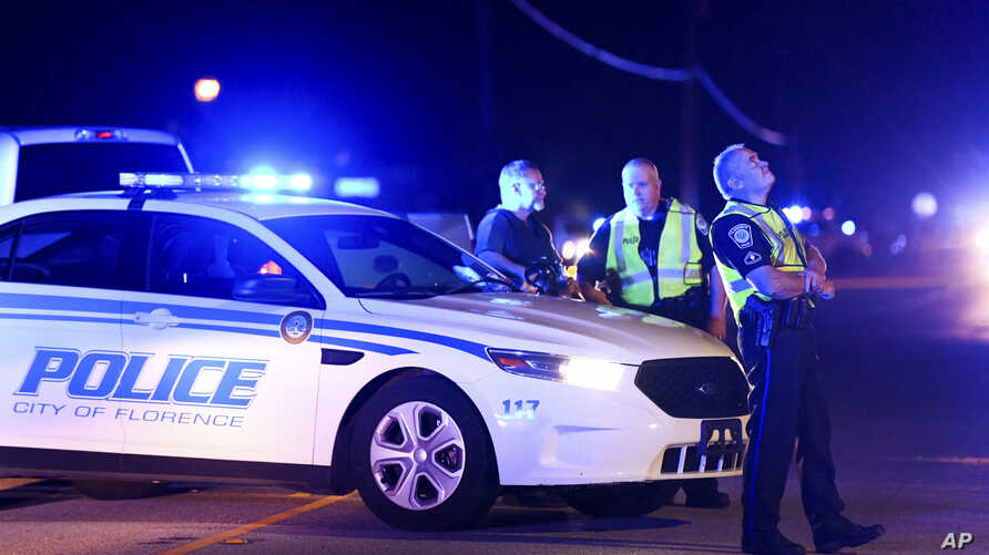 Authorities direct traffic on Hoffmeyer Road near the Vintage Place neighborhood where several law enforcement officers were shot, one fatally, Oct. 3, 2018, in Florence, S.C.