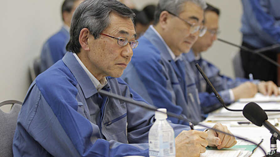 Tokyo Electric Power Co. (TEPCO) President Masataka Shimizu, left, attends a news conference with TEPCO Executive Toshio Nishizawa, center, on its fiscal 2010 earning at the company's head office in Tokyo, May 20, 2011