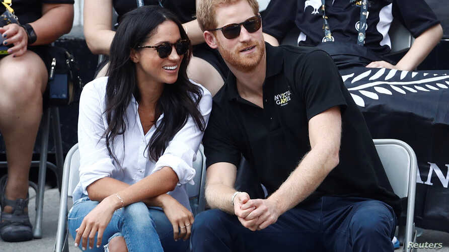 Britain's Prince Harry sits with girlfriend actress Meghan Markle to watch a wheelchair tennis event during the Invictus Games in Toronto, Sept. 25, 2017.
