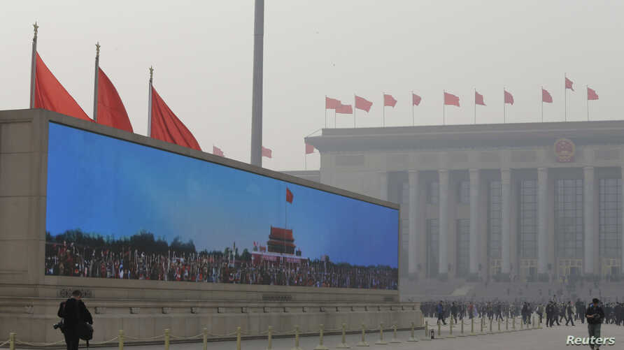 A large screen shows Tiananmen Gate under blue skies at Beijing's Tiananmen Square as delegates arrive for a plenary session of the National People's Congress (NPC) at the Great Hall of the People (R) in the dust storm and haze, Mar. 8, 2013.