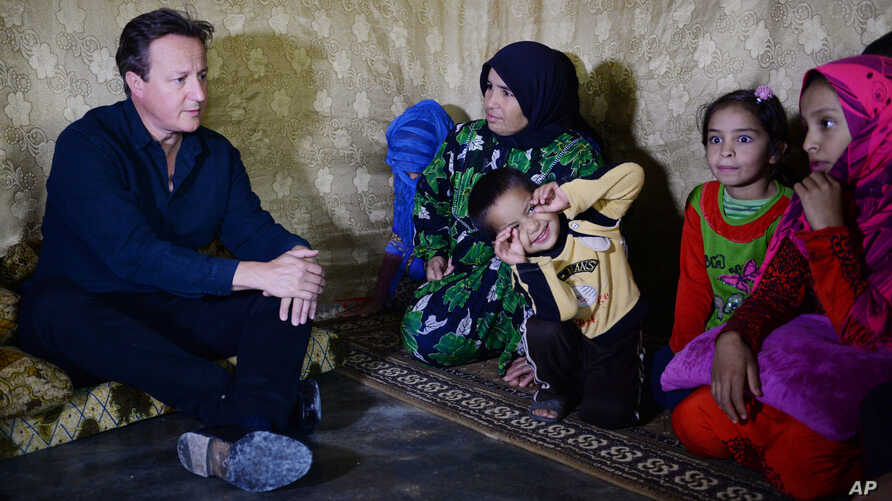 British Prime Minister David Cameron meets Syrian refugee families at a tented settlement camp in the Bekaa Valley on the Syrian - Lebanese border on Monday, Sept. 14, 2015.