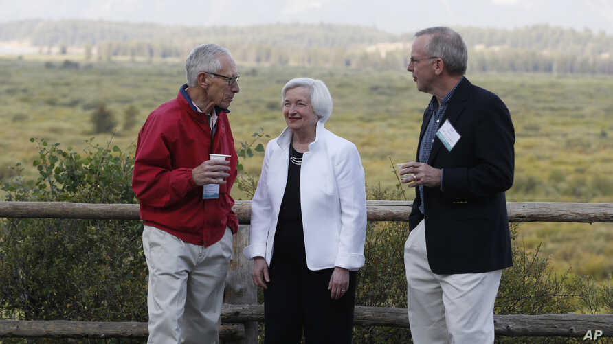 Federal Reserve Chair Janet Yellen, center, Stanley Fischer, left, vice chairman of the Board of Governors of the Federal Reserve System, and Bill Dudley, the president of the Federal Reserve Bank of New York, stroll together before Yellen's speech t...