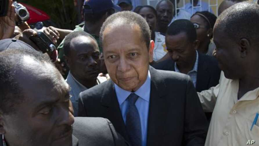 Former Haitian dictator Jean-Claude Duvalier, center, leaves Canape Vert Hospital in Port-au-Prince, Haiti, March 29, 2011