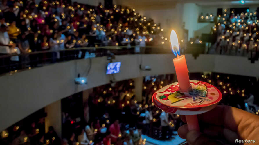A man holds a candle at a prayer service during Christmas Eve at a church in Bandung, Indonesia, Dec. 24, 2017. Antara Foto/Novrian Arby/ via Reuters