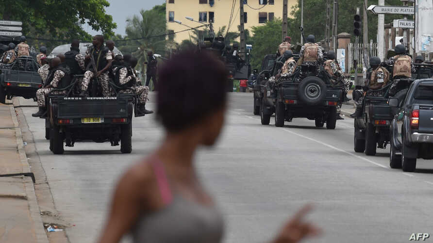 A woman walks past Ivorian soldiers patroling by Ivory Coast's army headquarters, the Gallieni military camp,  after they fired shots into the air in Abidjan, May 12, 2017.