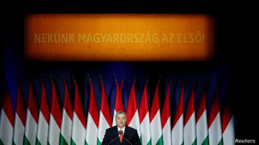 """Hungarian Prime Minister Viktor Orban delivers his annual state of the nation speech in Budapest, Hungary, Feb. 18, 2018. Slogan reads """"For us, Hungary first!"""""""