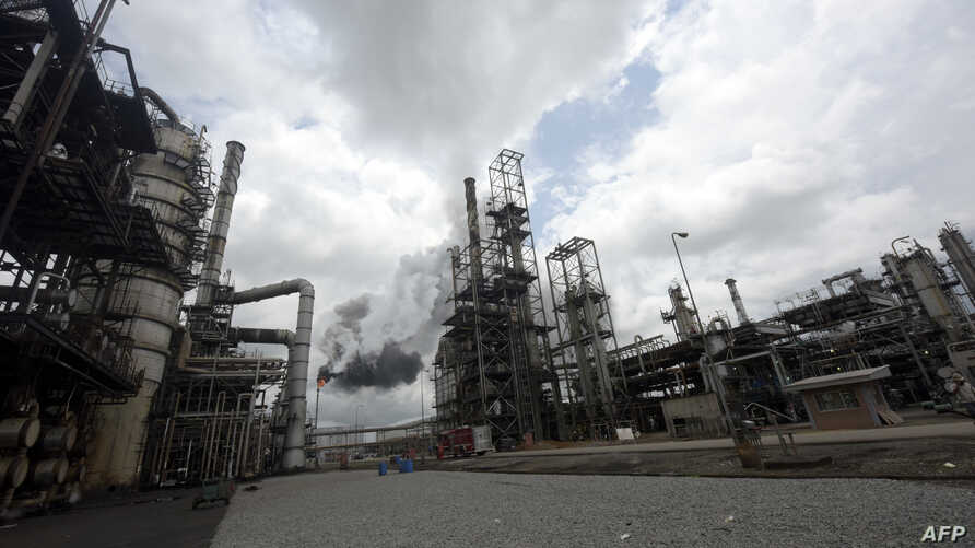 FILE - Thick black smoke billows from a pencil-thin chimney at the Port Harcourt Refining Company Limited, Rivers State on Sept. 16, 2015. The Port Harcourt refinery is Nigeria's oldest, built in 1965. In recent years, however, it became a byword for...
