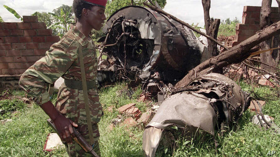 FILE - A Rwanda Patriotic Front (RPF) rebel walks by the the site of a April 6 plane crash which killed Rwanda's President Juvenal Habyarimana in this May 23, 1994 file photo in Kigali.