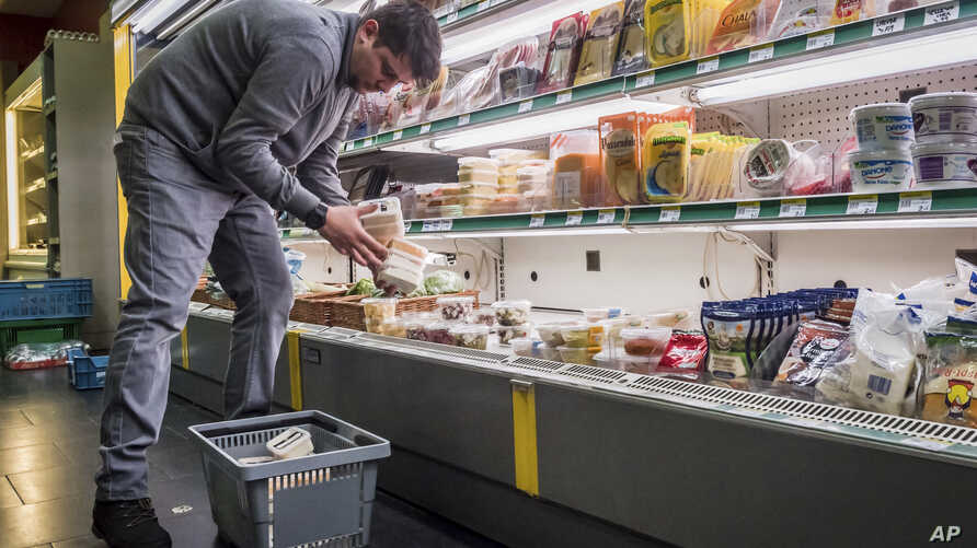 FILE - A worker removes expired food in a local supermarket in Brussels, Jan. 16, 2017.