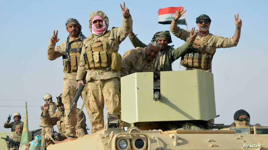 Iraqi forces show victory signs after they captured Rawa town, the last remaining town under Islamic State control, Nov. 17, 2017.