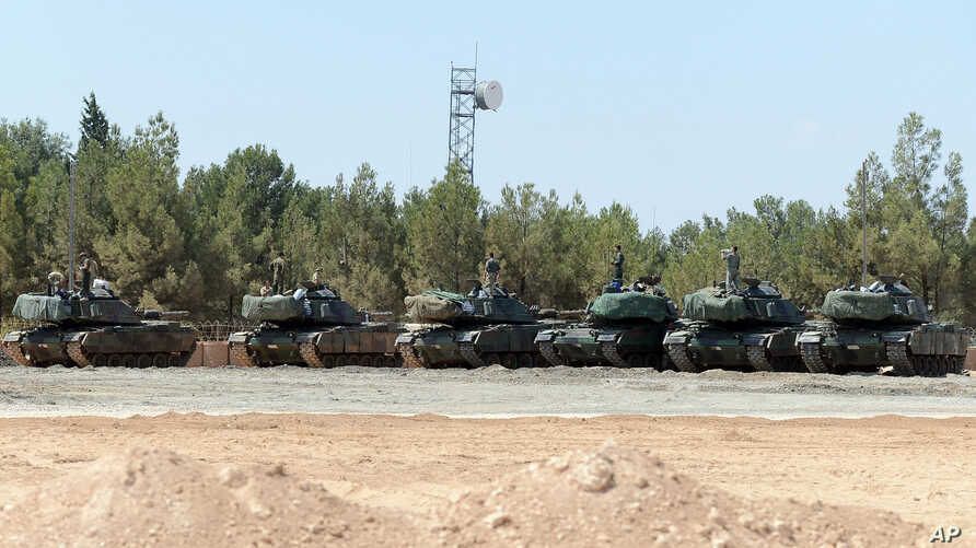 "FILE - Turkish tanks stationed near the Syrian border, in Karkamis, Turkey, Sept. 3, 2016. Turkey's state-run news agency says Turkish tanks have entered Syria's Cobanbey district northeast of Aleppo in a ""new phase"" of the Euphrates Shield operation"