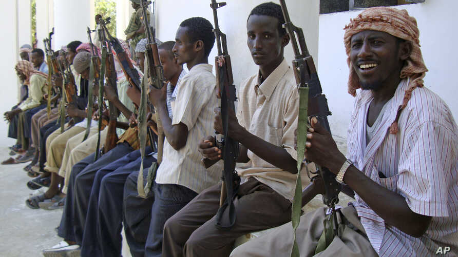 FILE- Armed men from the al-Shabab militant group are paraded at the presidential palace in Mogadishu, Somalia, after defecting from the al-Qaida-linked group to join government forces, Oct. 13, 2009.