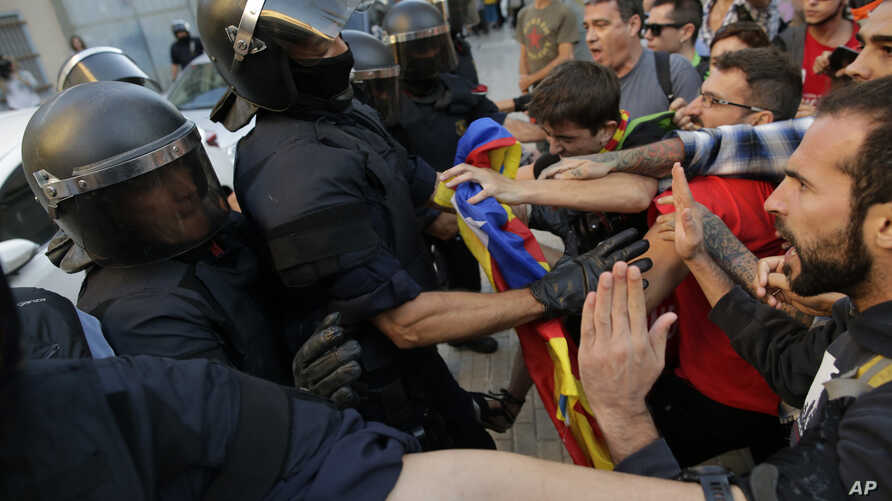 Mossos d'Esquadra police officers scuffle with protesters during a demonstration supporting Catalonia's independence referendum in Terrassa, Spain, Sept. 19, 2017.