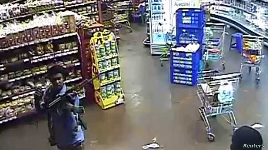 In this photo taken from footage from Citizen TV, via the Kenya Defense Forces and made available Oct. 4 2013,  a man reported to be Omar Abdul Rahim Nabhan, walka in a store at the Westgate Mall, prior to the four-day-long siege in Nairobi, Kenya.