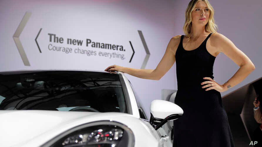 Tennis star Maria Sharapova poses with the 2017 Porsche Panamera during the Los Angeles Auto Show Wednesday, Nov. 16, 2016, in Los Angeles.