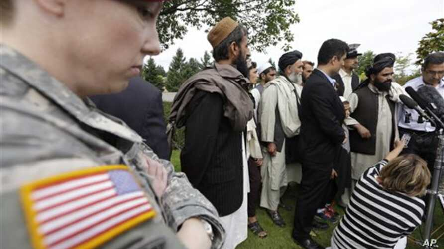 A U.S. soldier looks on as Afghan villagers, some of whom testified earlier in the week, speak through an interpreter with reporters, following a sentencing hearing for Staff Sgt. Robert Bales at Joint Base Lewis-McChord, Washington, Aug. 23, 2013. B