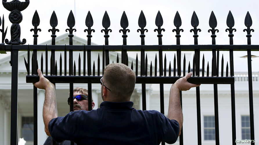 FILE - U.S. government contractors begin the installation of additional security spikes on the existing White House perimeter fence in Washington, July 1, 2015.
