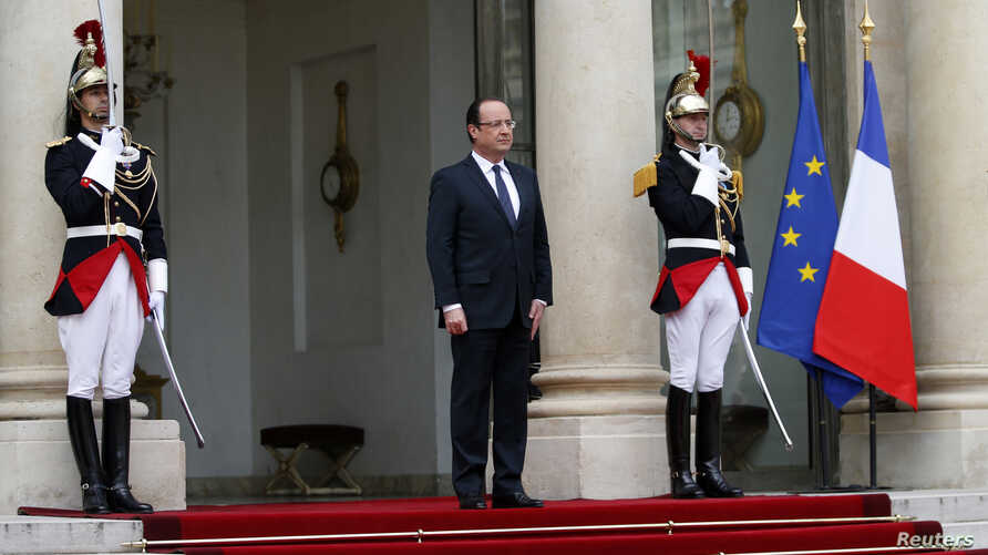 French President Francois Hollande stands outside the Elysee Palace as he waits for the arrival of a guest in Paris May 7, 2013.