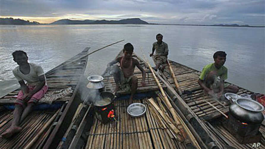 Fishermen prepare food on their boat on the River Brahmaputra in Gauhati, in the northeastern Indian state of Assam, June 15, 2011