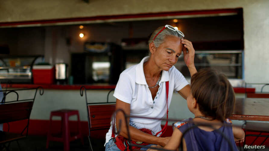Zulay Pulgar, 43, rest in a coffee shop with her son Emmanuel, 4, after standing in line to buy cement in a hardware store in Punto Fijo, Venezuela, Nov. 17, 2016.