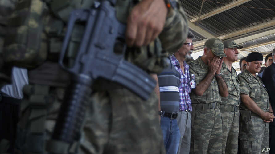 Turkish soldiers pray during the funeral of soldier Mehmet Yalcin Nane, killed July 23 by IS militants when they attacked a Turkish military outpost at the border with Syria, in the town of Gaziantep, southeastern Turkey, July 24, 2015.
