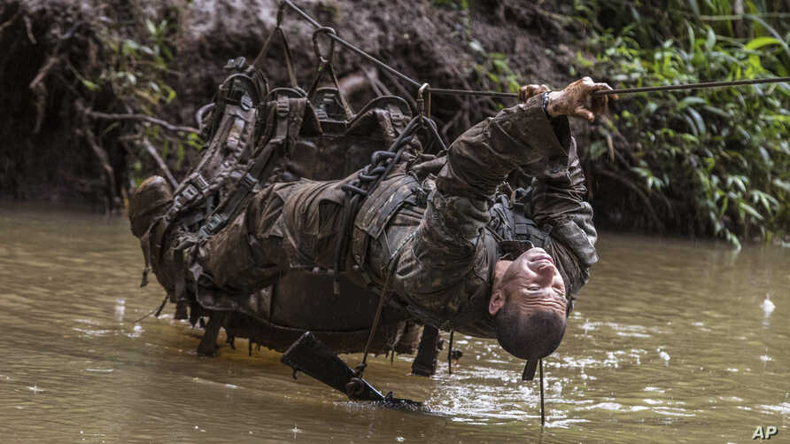 A soldier from the U.S. Army's 25th Infantry Division 1st Stryker Brigade Combat Team crosses a stream with a rope during jungle warfare training at Schofield Barracks, Hawaii, March 1, 2017.
