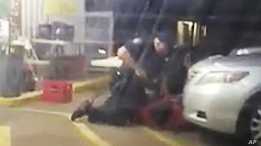 FILE - Image made from video shows Alton Sterling being restrained by two Baton Rouge police officers, one holding a gun, outside a convenience store in Baton Rouge, La., July 5, 2016, before one of the officers shot and killed Sterling, a black man