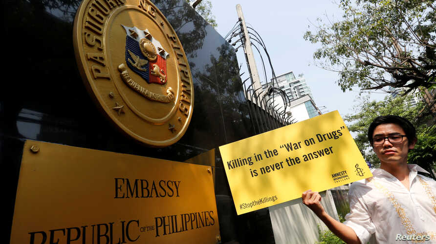 FILE - An activist from Amnesty International Thailand holds a banner during a rally to urge the Phillipines to stop 'War on Drugs' in front of Philippines's embassy in Bangkok, Thailand, April 25, 2017.