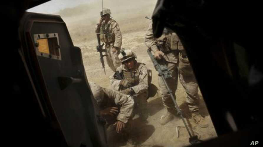 United States Marines from Bravo Company of the 1st Battalion of the 2nd Marines take cover outside their vehicle as a medevac helicopter leaves the scene with a wounded colleague following an IED strike near Musa Qaleh, in northern Helmand Province,