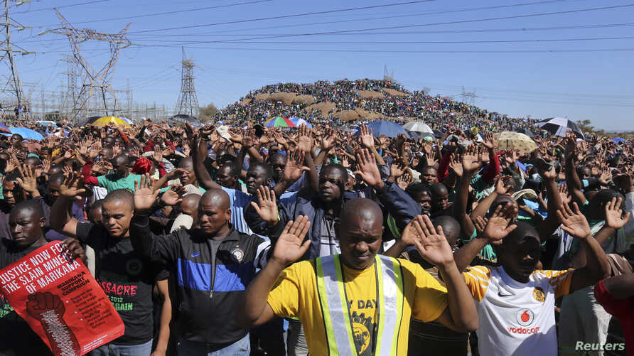 Miners gesture as they pray during the one-year anniversary commemorations to mark the killings of 34 striking platinum miners fatally shot by police outside the Lonmin's Marikana platinum mine in Rustenburg, 100 kilometers northwest of Johannesburg,