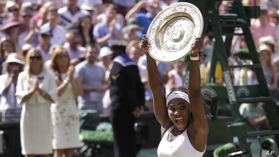 Serena Williams of the United States reacts as she holds up the trophy after winning the women's singles final against Garbine Muguruza of Spain, at the All England Lawn Tennis Championships in Wimbledon, London, July 11, 2015.