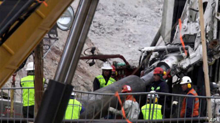 Rescue workers insert steel pipes to encase the escape tunnel that will be used to free trapped miners at the San Jose mine near Copiapo, Chile. 10 Oct 2010.