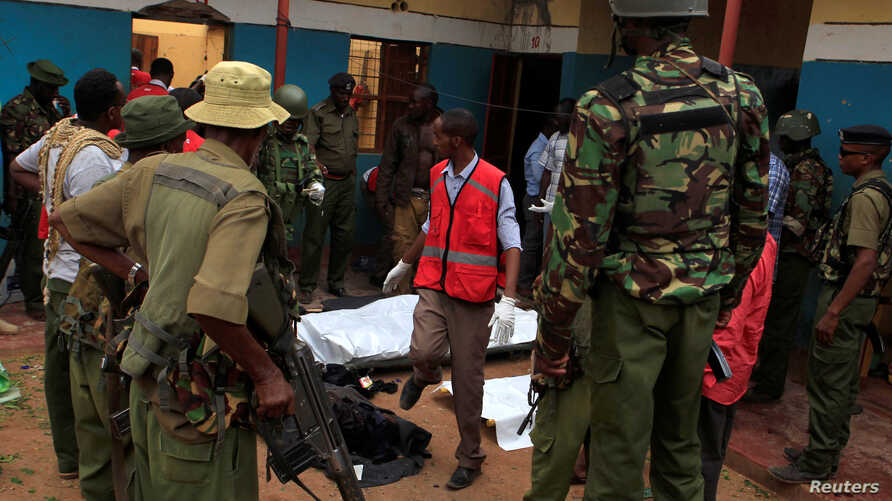 Police officers stand by dead bodies after an attack by Islamist militants from the Somali group al-Shabab in Mandera, Kenya, Oct. 6, 2016.
