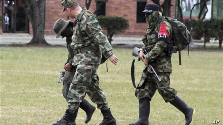 Colombian soldier, left front, escorts rebels of the National Liberation Army, ELN, who gave themselves up at a military base in Cali, July 16, 2013.