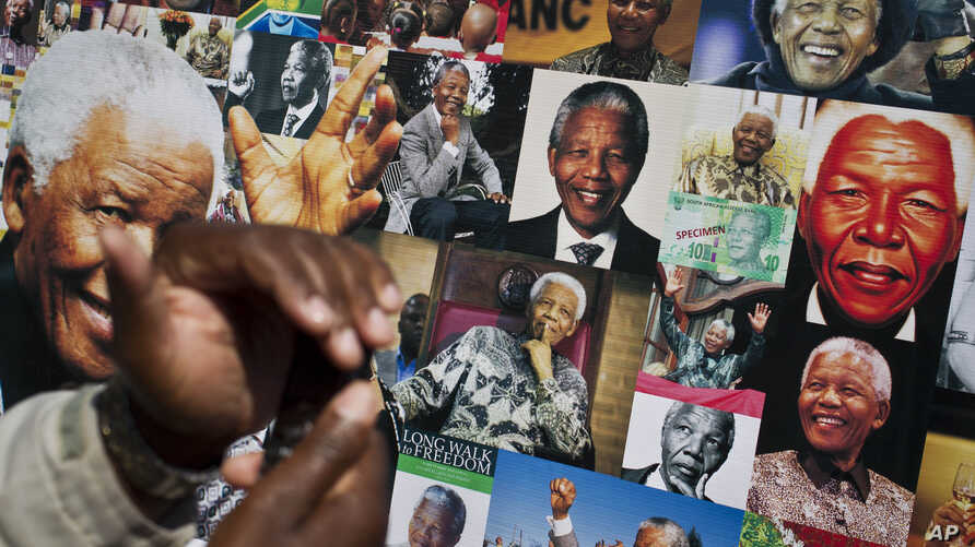 A well-wisher uses his phone to take a picture of a banner of photos of Nelson Mandela, outside the Mediclinic Heart Hospital where former South African President Nelson Mandela is being treated in Pretoria, South Africa Thursday, July 18, 2013. Sout