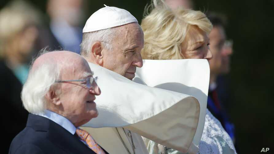 Pope Francis, center, is flanked by Irish President Michael D. Higgins, left, and President's wife Sabina, upon his arrival at the Presidential residence in Dublin, Ireland, Aug. 25, 2018.