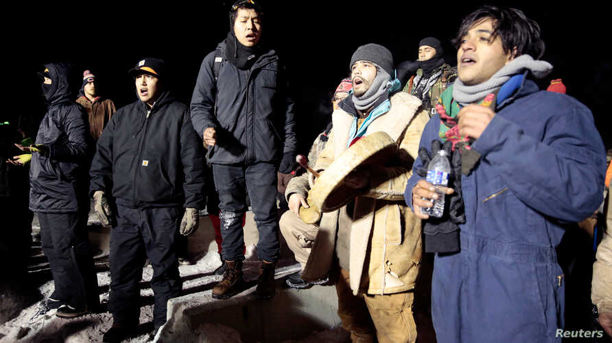 Opponents of the Dakota Access oil pipeline sing during a confrontation with police on Backwater Bridge near Cannon Ball, N.D., Jan. 19, 2017.