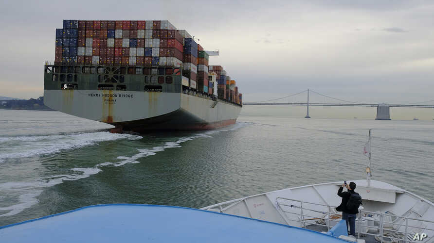 FILE- In this March 7, 2018, file photo, a man standing on the bow of a Golden Gate Ferry takes a picture of a container ship as it heads toward the San Francisco-Oakland Bay Bridge in San Francisco.