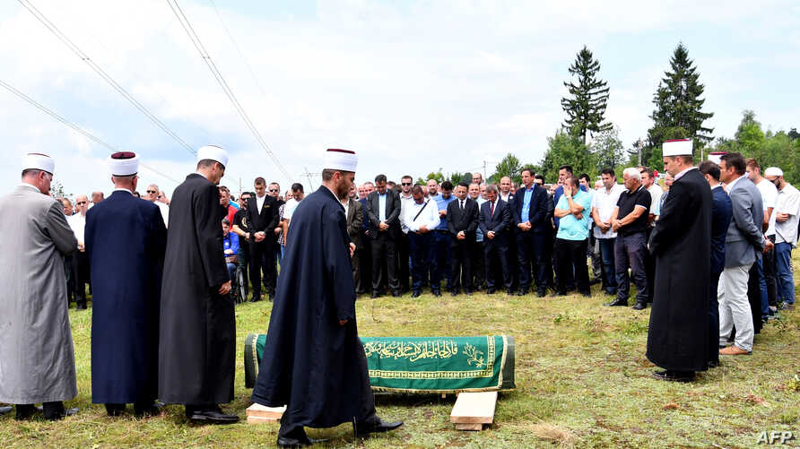 Bosnian Muslims gather near a graveyard to pay respects and lay to rest the late Hatidza Mehmedovic, in the village of Suceska, near Srebrenica, July 25, 2018.