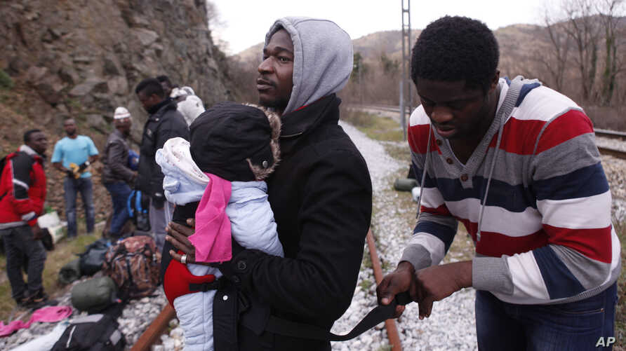 FILE - A migrant from Cameroon helps other migrants on their way to the town of Evzonoi, Greece, Feb. 28, 2015.