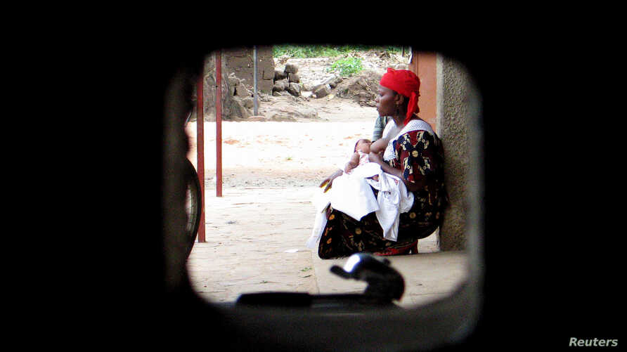 FILE - A woman sits with her child at a health clinic in Bujumbura, Burundi, Apr. 18, 2006. More than one million people die from malaria every year, almost 90 percent are in Africa.