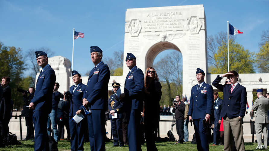 US Air Force soldiers watch an aerial parade during a ceremony honoring the lives of the American pilots who volunteered to fight for France during World War I, in Marne la Coquette, outside Paris, Wednesday, April 20, 2016.