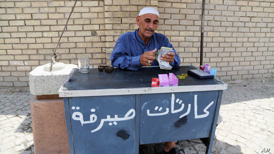 An Iraqi street currency exchanger counts banknotes in Baghdad, Iraq, Aug. 8, 2015.