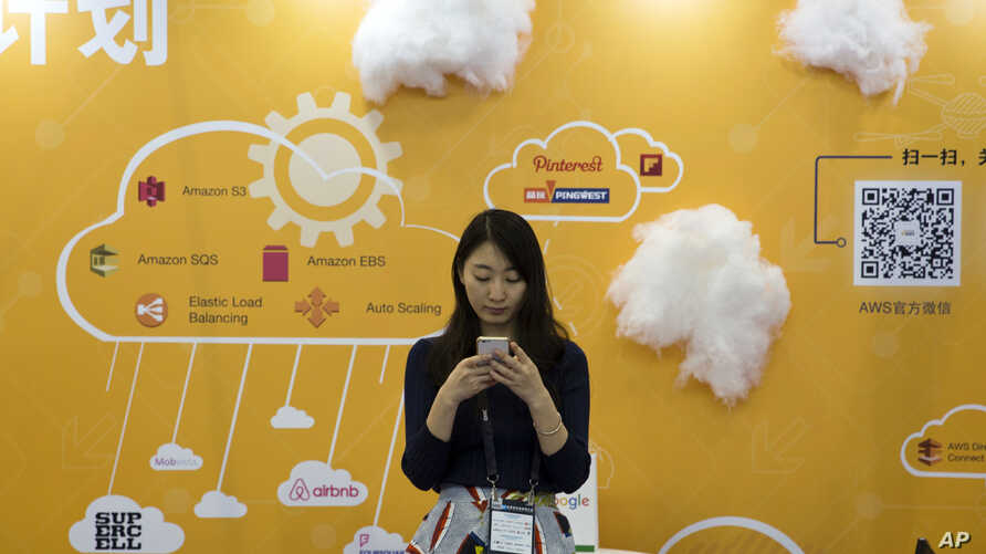 FILE - A woman uses her smartphone near a booth promoting cloud services during the Global Mobile Internet Conference in Beijing, China.