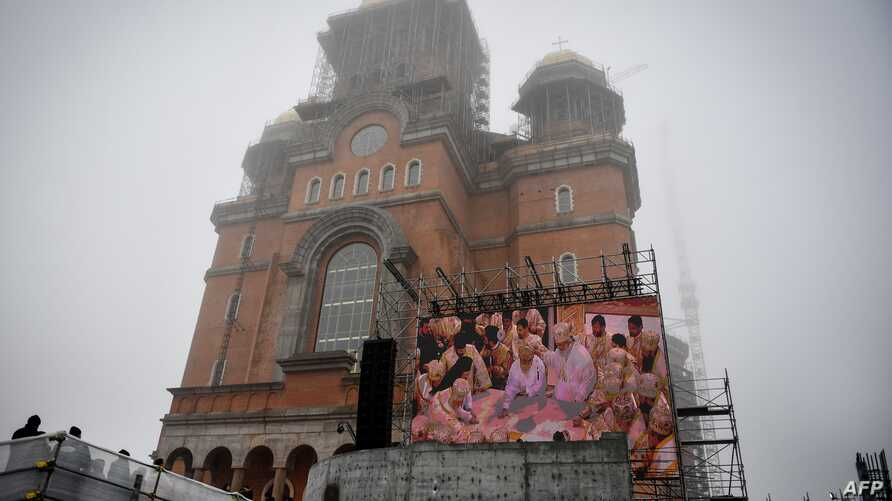 A screen streams the consacration service of the Romanian People's Salvation Cathedral still under construction in Bucharest, Nov. 25, 2018.